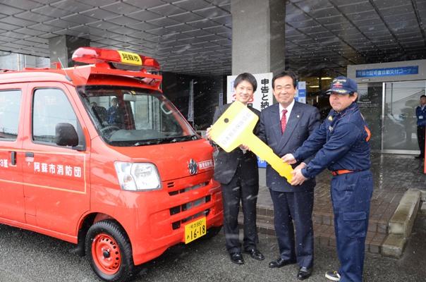 消防自動車の鍵を贈る井瀧事務局長(左)と受け取る佐藤市長(中)高宮消防団長(右)